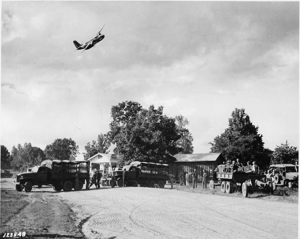 Red Army bombers dropping flour bombs on Blue Army troops and Addison's Store during the Battle of Mount Carmel. Note the traffic congestion on the roadway. (Robertson Collection)